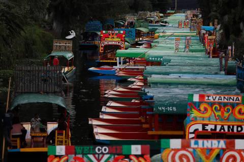 Gondoleros poseen trajineras, botes de madera pintados de colores populares entre turistas y ju ...