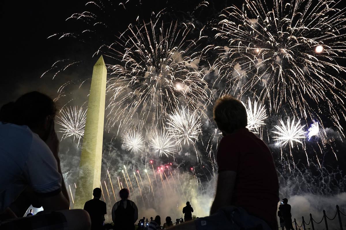 Fuegos artificiales iluminan el cielo alrededor del Monumento a Washington después de que el p ...