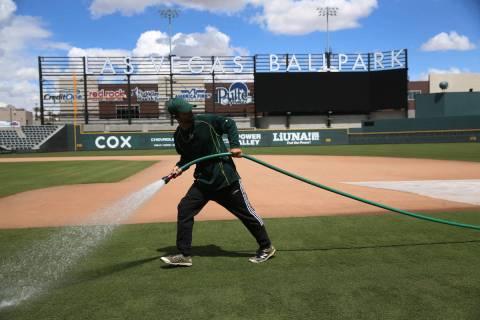 El jardinero Logan Mace rocía agua en el campo del estadio de Las Vegas el jueves, 9 de abril ...