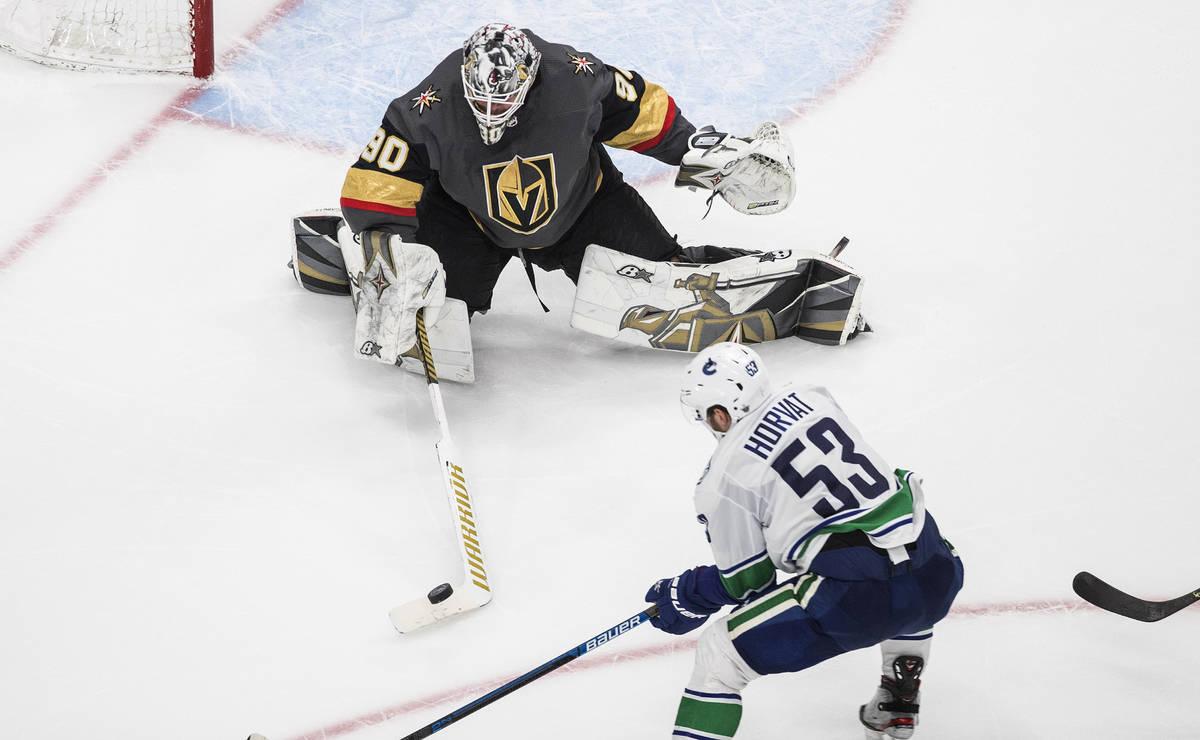 Bo Horvat de los Canucks de Vancouver (53) es detenido por el portero de los Golden Knights de ...