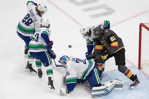 El portero de los Canucks de Vancouver, Thatcher Demko (35), hace una atajada mientras los juga ...