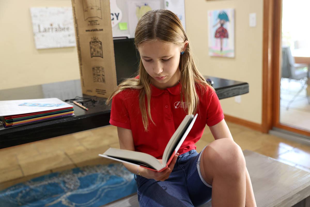 Lily Larrabee, de 10 años, estudiante de Legacy Traditional School, lee un libro después de t ...