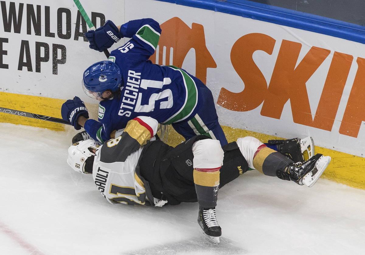 Troy Stecher de los Vancouver Canucks (51) taclea a Jonathan Marchessault de los Vegas Golden K ...