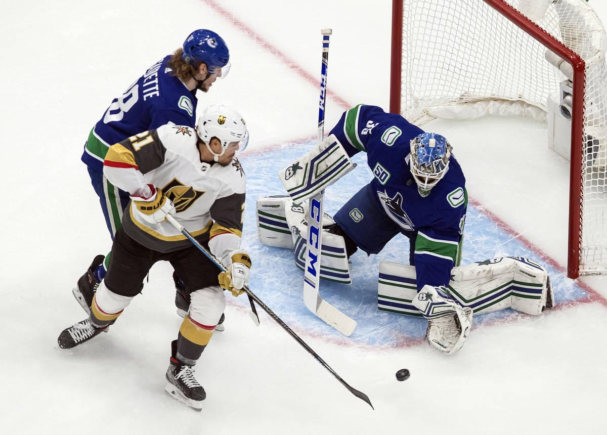 El portero de los Canucks de Vancouver, Thatcher Demko (35), hace una atajada contra Nick Cousi ...