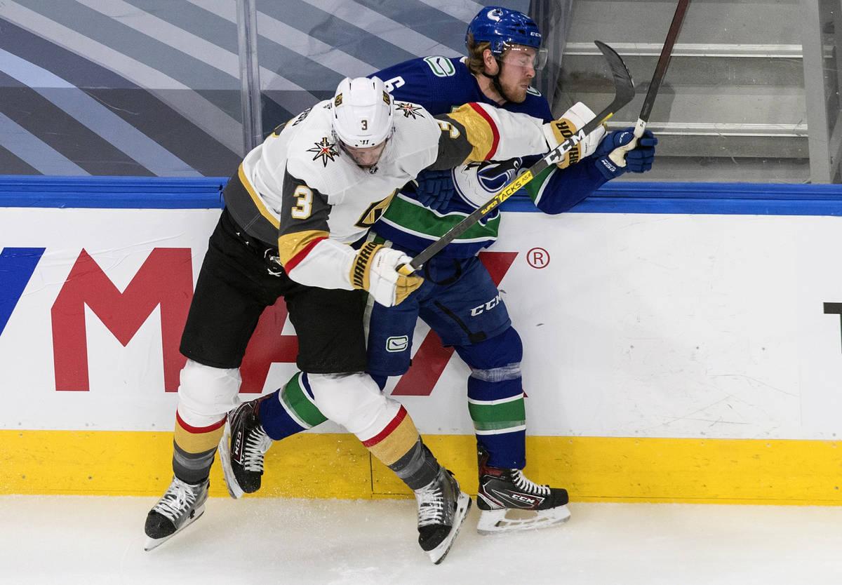 Brock Boeser de los Vancouver Canucks (6) es derribado por Brayden McNabb de los Golden Knights ...