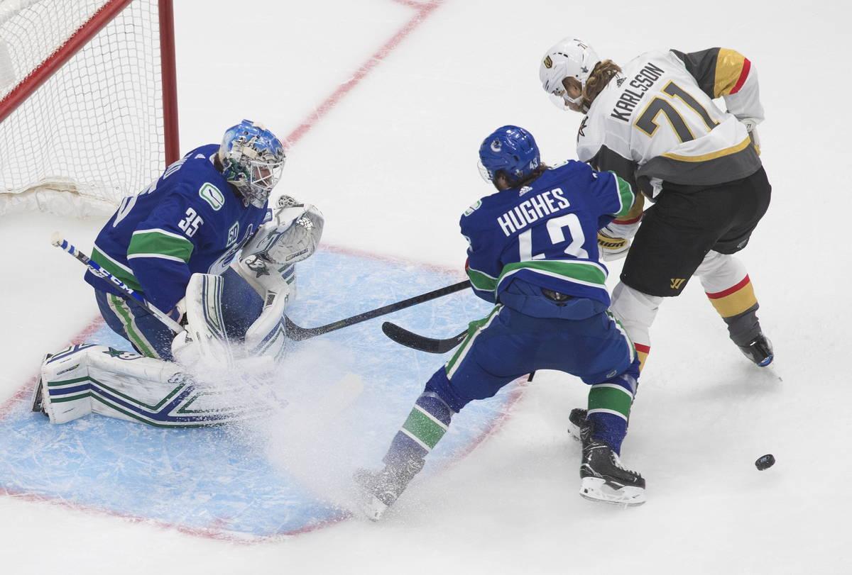 El portero de los Canucks de Vancouver, Thatcher Demko (35), hace una atajada mientras William ...