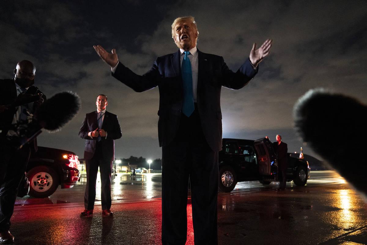 El presidente Donald Trump habla con los reporteros en la Base Aérea Andrews después de asist ...
