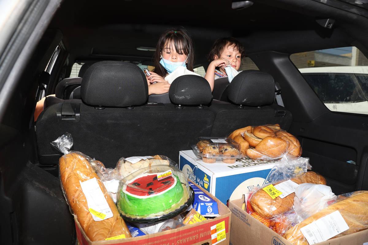 Zamira, de cinco años, y su hermana Zeriah Basulto de Las Vegas, miran la comida que su famili ...