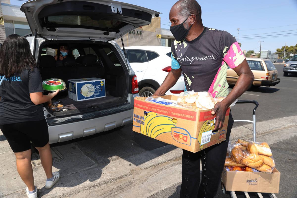 El voluntario Gregory Jones, a la derecha, ayuda a Wendy Basulto a llevar comida a su coche en ...