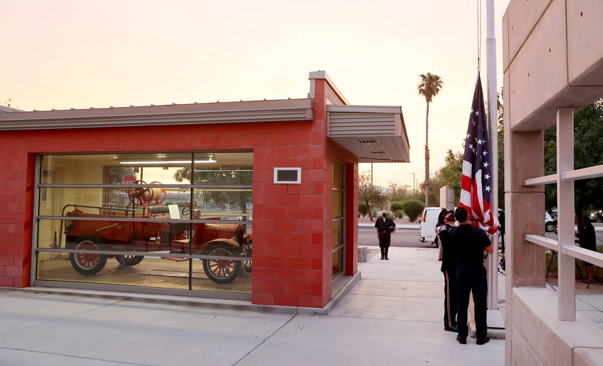Los bomberos bajan la bandera en preparación para izar una bandera que ondeó en el World Trad ...