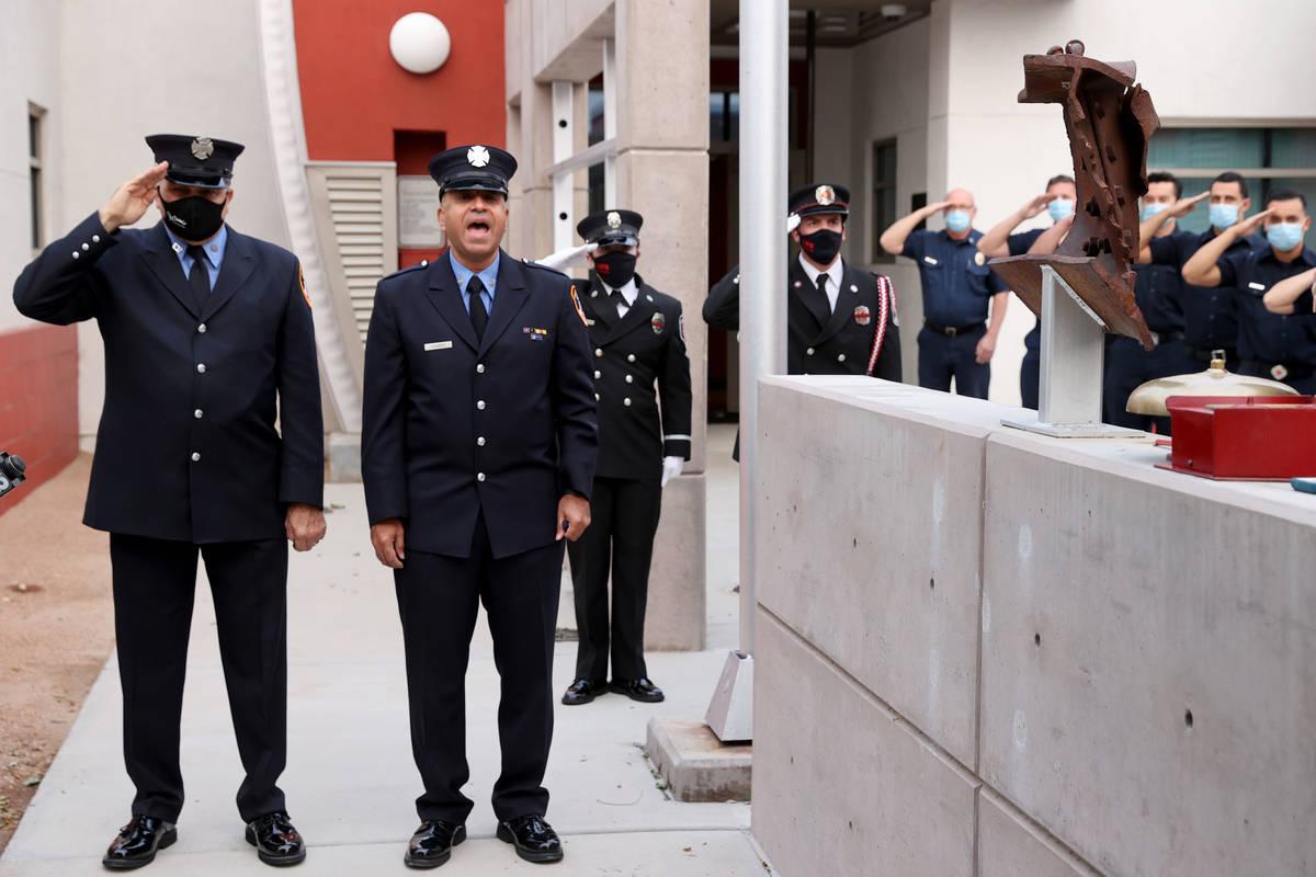 El bombero retirado de Nueva York, Frank Pizarro, de Las Vegas, segundo a la izquierda, canta d ...