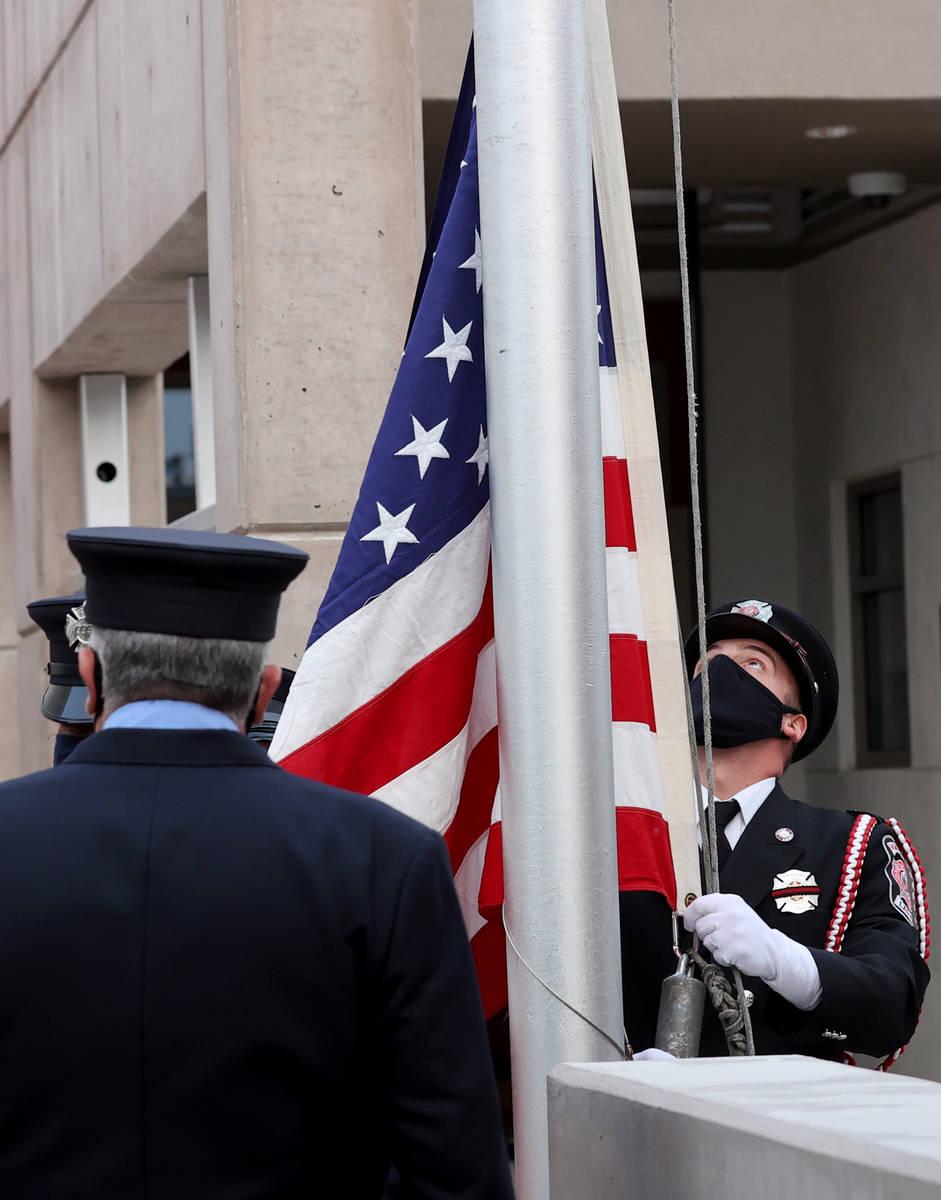El ingeniero de bomberos de Las Vegas, Brian Dietz, se prepara para izar una bandera que ondeó ...