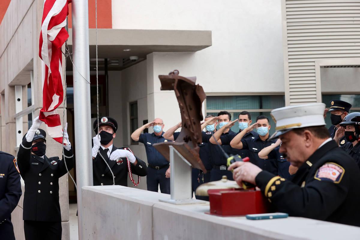 La bombera de Las Vegas, Lisa Leonard, izquierda, y el ingeniero, Brian Dietz, izan una bandera ...