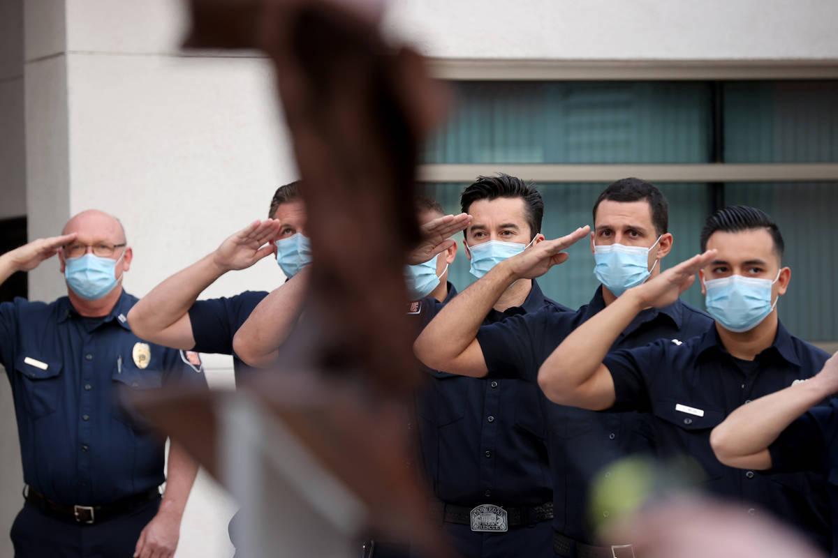 Bomberos de Las Vegas saludan a la bandera estadounidense frente a un pedazo del World Trade Ce ...