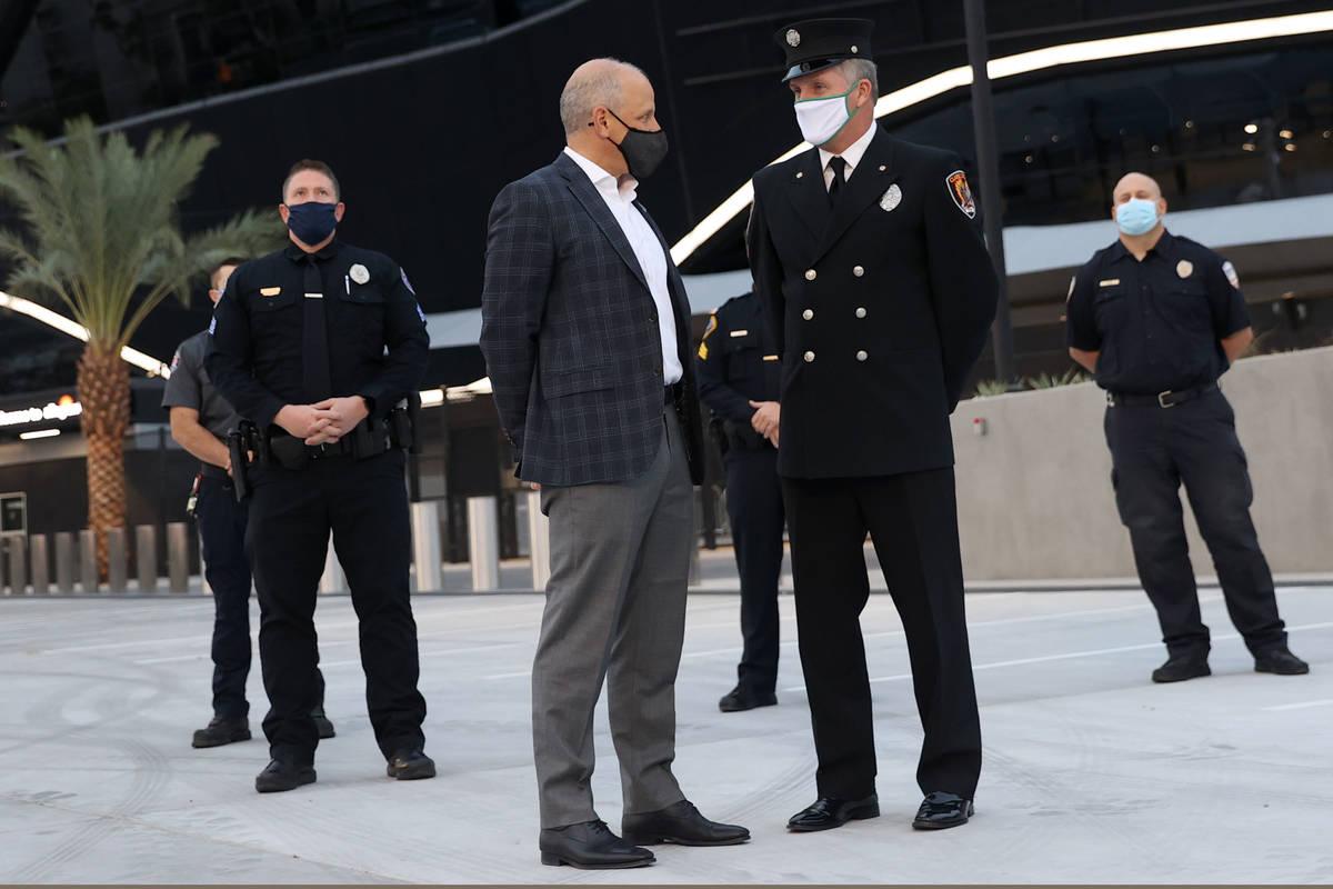 El presidente de los Raiders de Las Vegas, Marc Badain, izquierda, habla con el bombero del Dep ...
