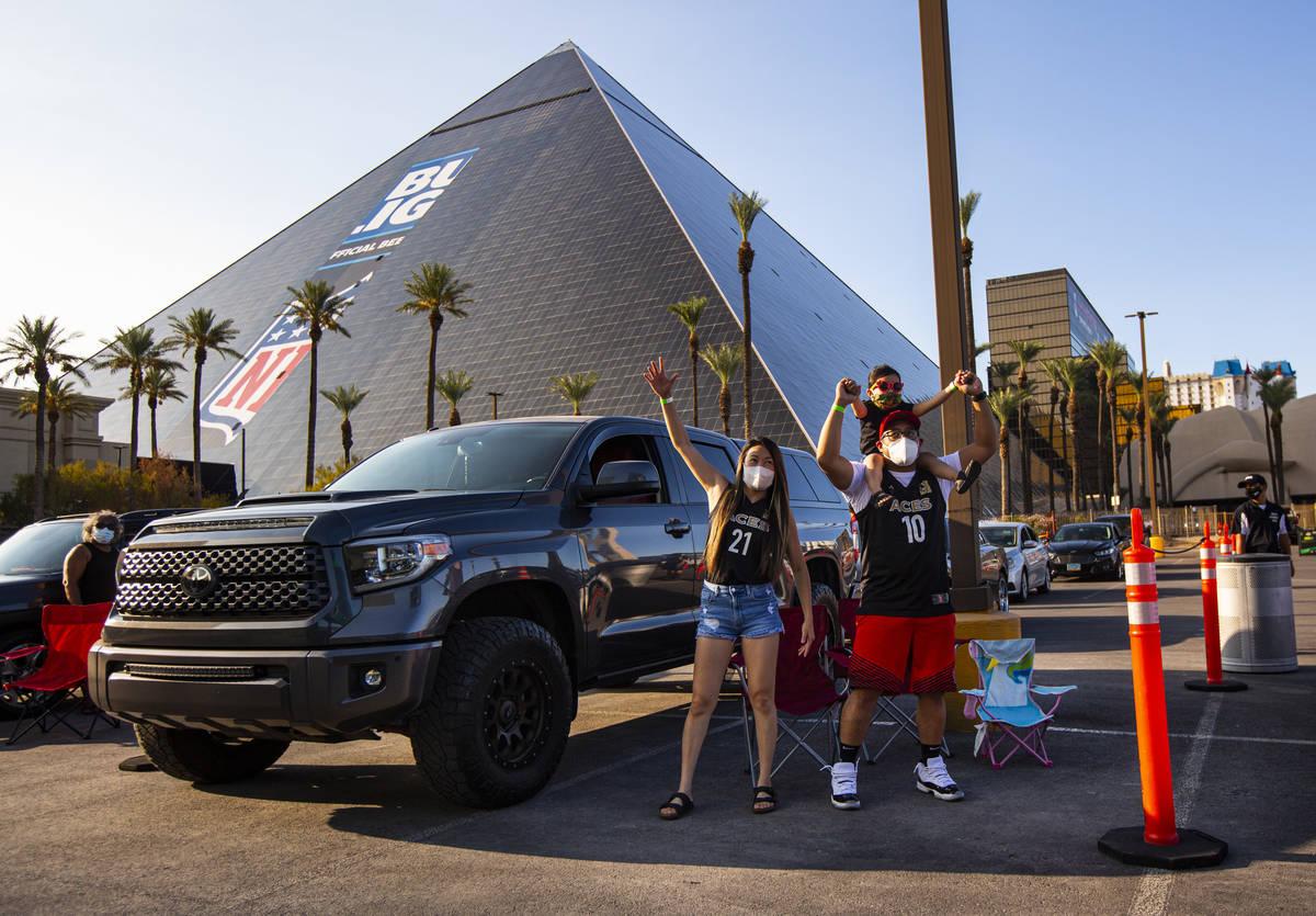 Los fans de Las Aces de Las Vegas, Kris Gabriel, izquierda, y Aubrey Gabriel, de 3 años, soste ...