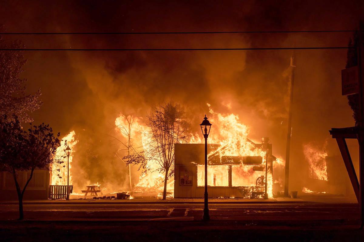 Los edificios están envueltos en llamas mientras un incendio forestal asola la ciudad de Talen ...