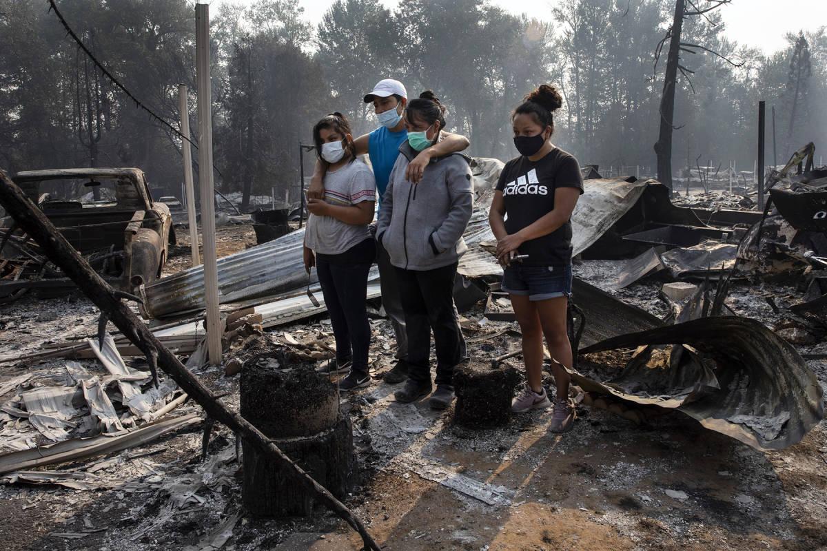 La familia Reyes mira la destrucción de su casa en el parque de casas móviles de Coleman Cree ...