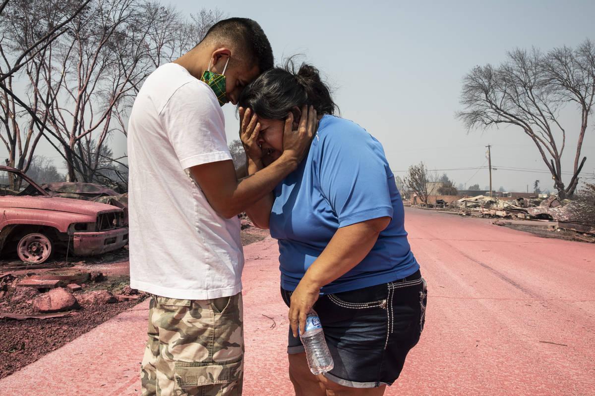 Dora Negrete es consolada por su hijo Héctor Rocha después de ver su casa rodante destruida e ...