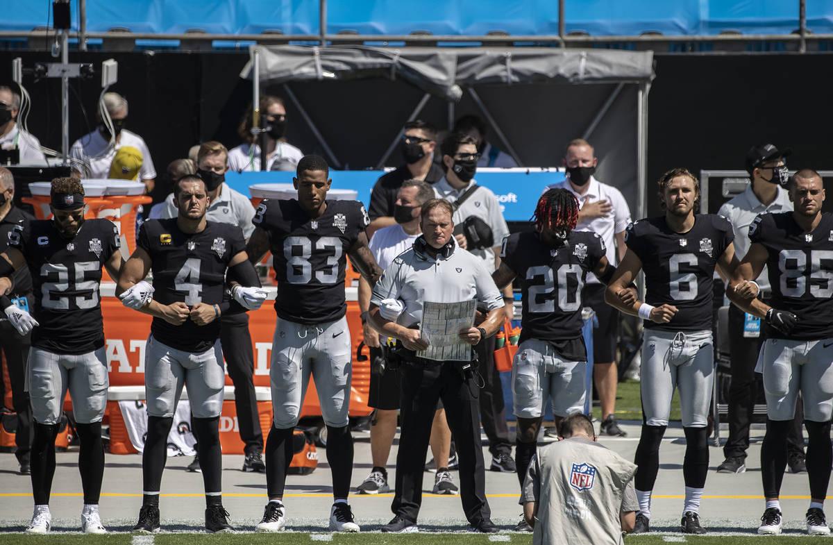 El entrenador de los Raiders de Las Vegas, John Gruden, al centro, se cruza de brazos con sus j ...