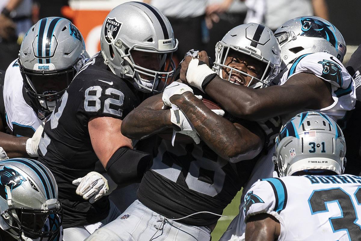El running back de los Raiders de Las Vegas, Josh Jacobs (28), es apilado por los defensores de ...