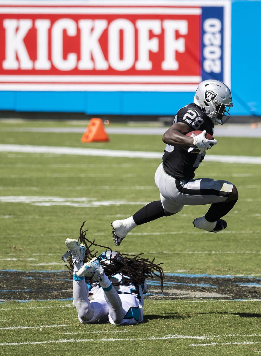 El corredor de los Raiders de Las Vegas, Josh Jacobs (28), salta sobre el safety de los Panther ...