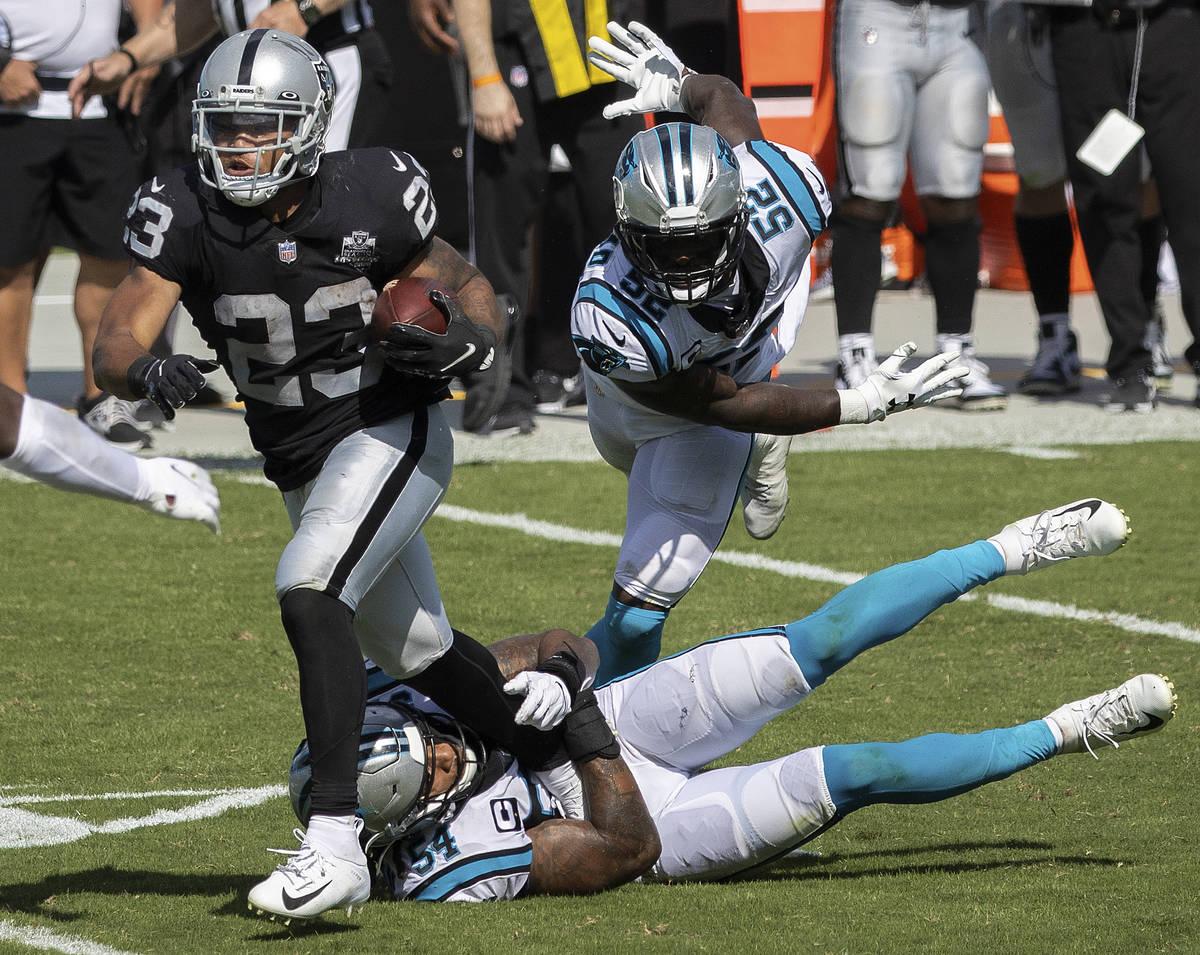 El running back de los Raiders de Las Vegas, Devontae Booker, lucha por una mayor distancia con ...