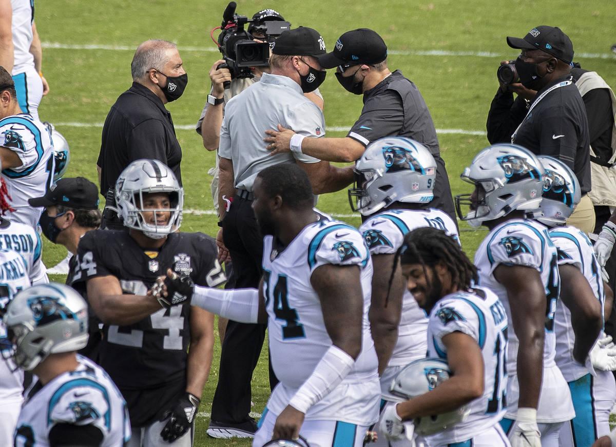El entrenador principal de los Raiders de Las Vegas, John Gruden, arriba/izquierda, da la mano ...