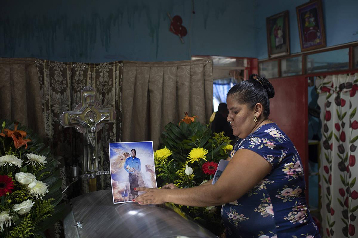 Una mujer coloca una foto del periodista asesinado Julio Valdivia en su ataúd durante un velor ...