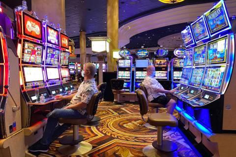 Los jugadores se ponen máscaras protectoras en el Caesars Palace de Las Vegas Strip, el 24 de ...