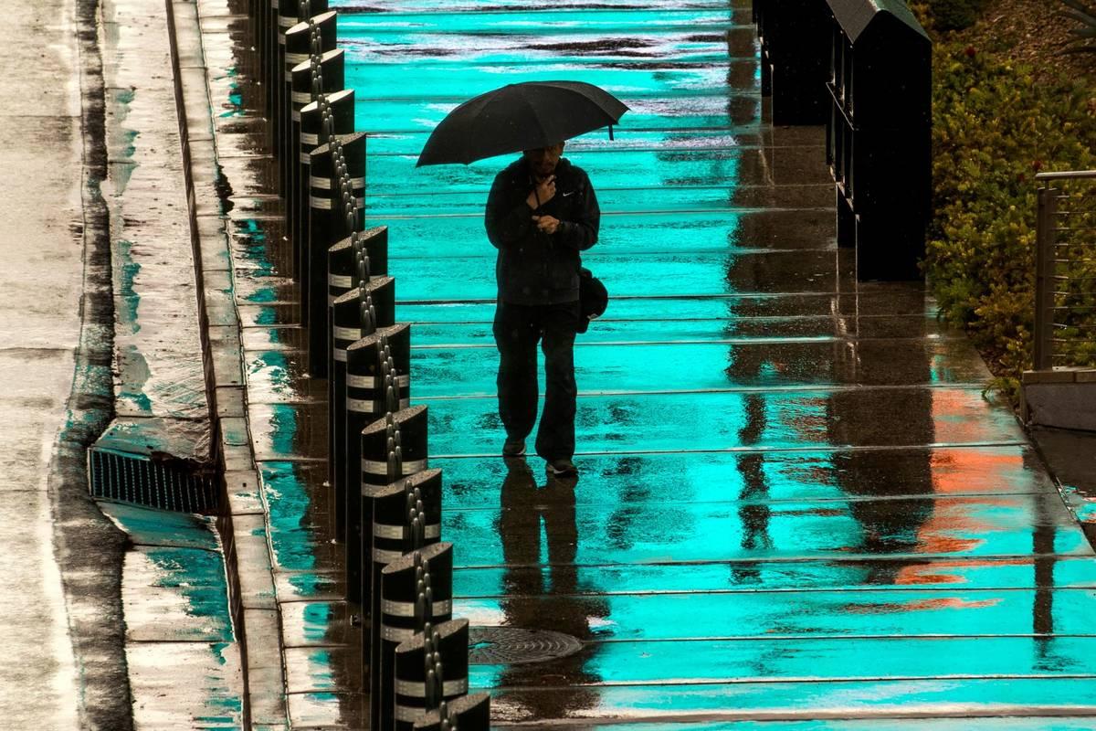 Un peatón es bañado por la luz azul de un letrero iluminado arriba mientras camina bajo la ll ...