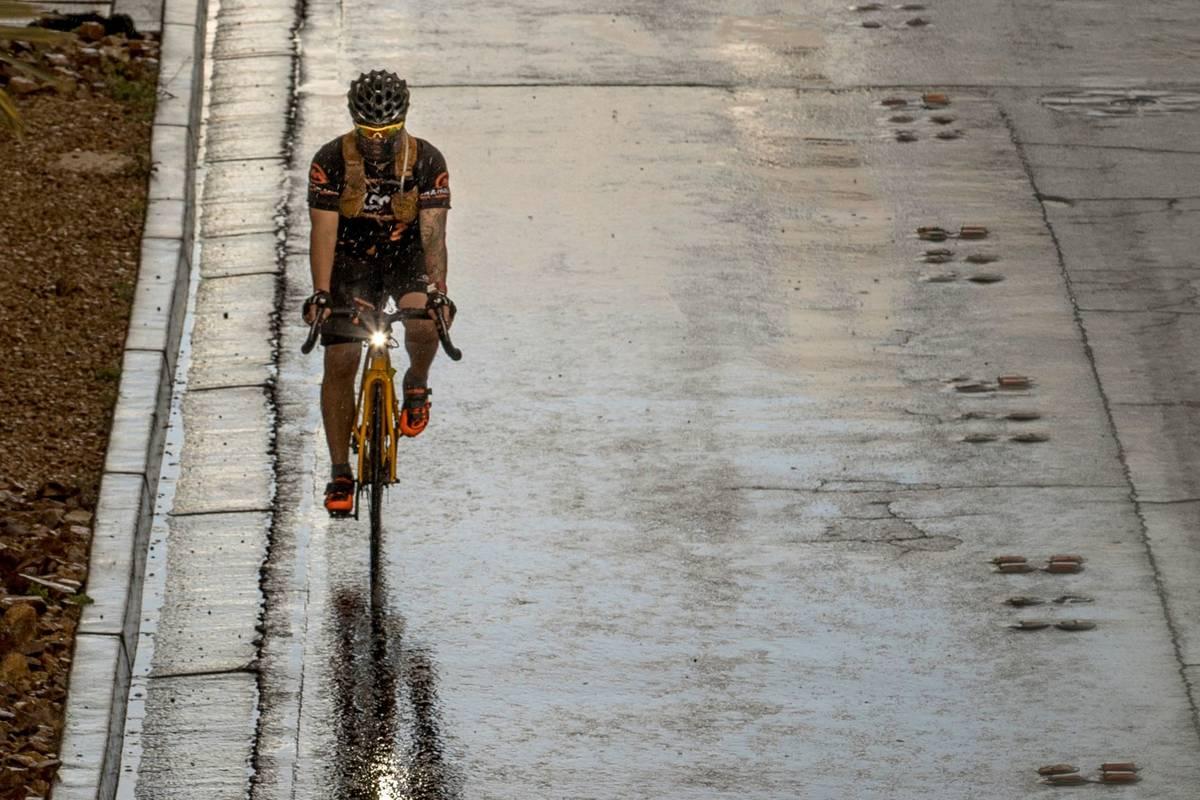 Un ciclista con cubrebocas transita bajo la lluvia en el Strip de Las Vegas pasando por el cent ...