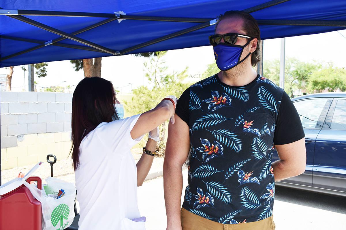 El integrante de REACH, Luis Aceves, es vacunado contra la influenza por parte de una enfermera ...