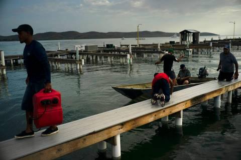 En esta foto de archivo, las personas llegan a un puerto privado para trasladar los botes en bu ...