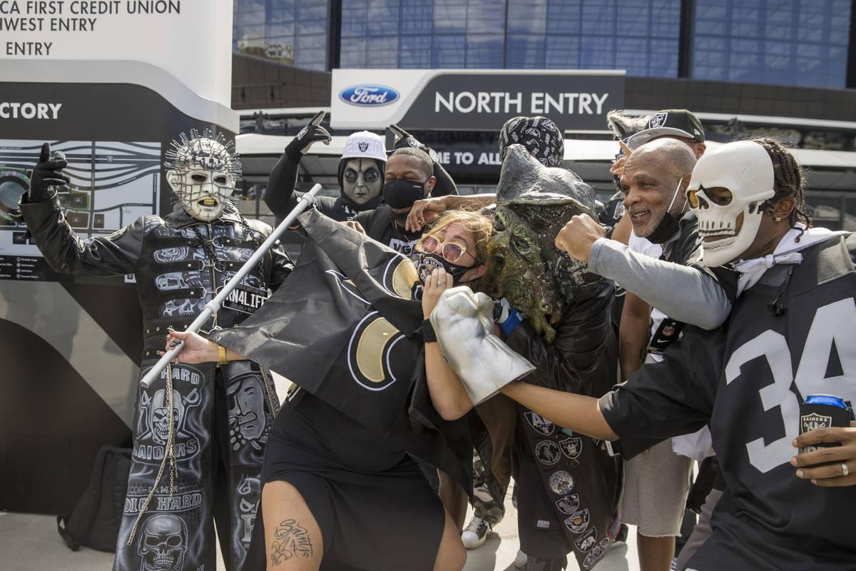 La fan de los New Orleans Saints, Amy Laughlin, rodeada por personajes de Los Raiders de Las Ve ...