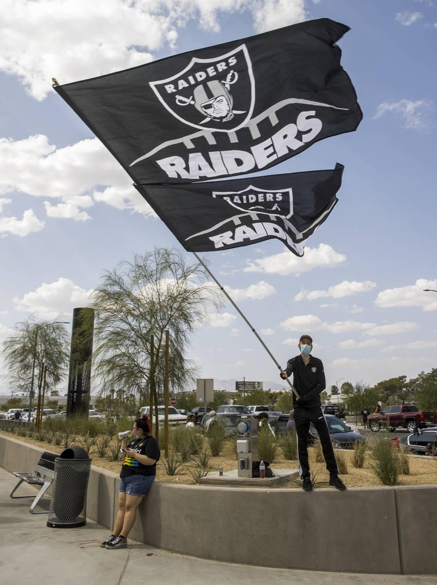 El fan de los Raiders de Las Vegas, Matt Helfst, ondea una bandera gigante mientras él y otros ...