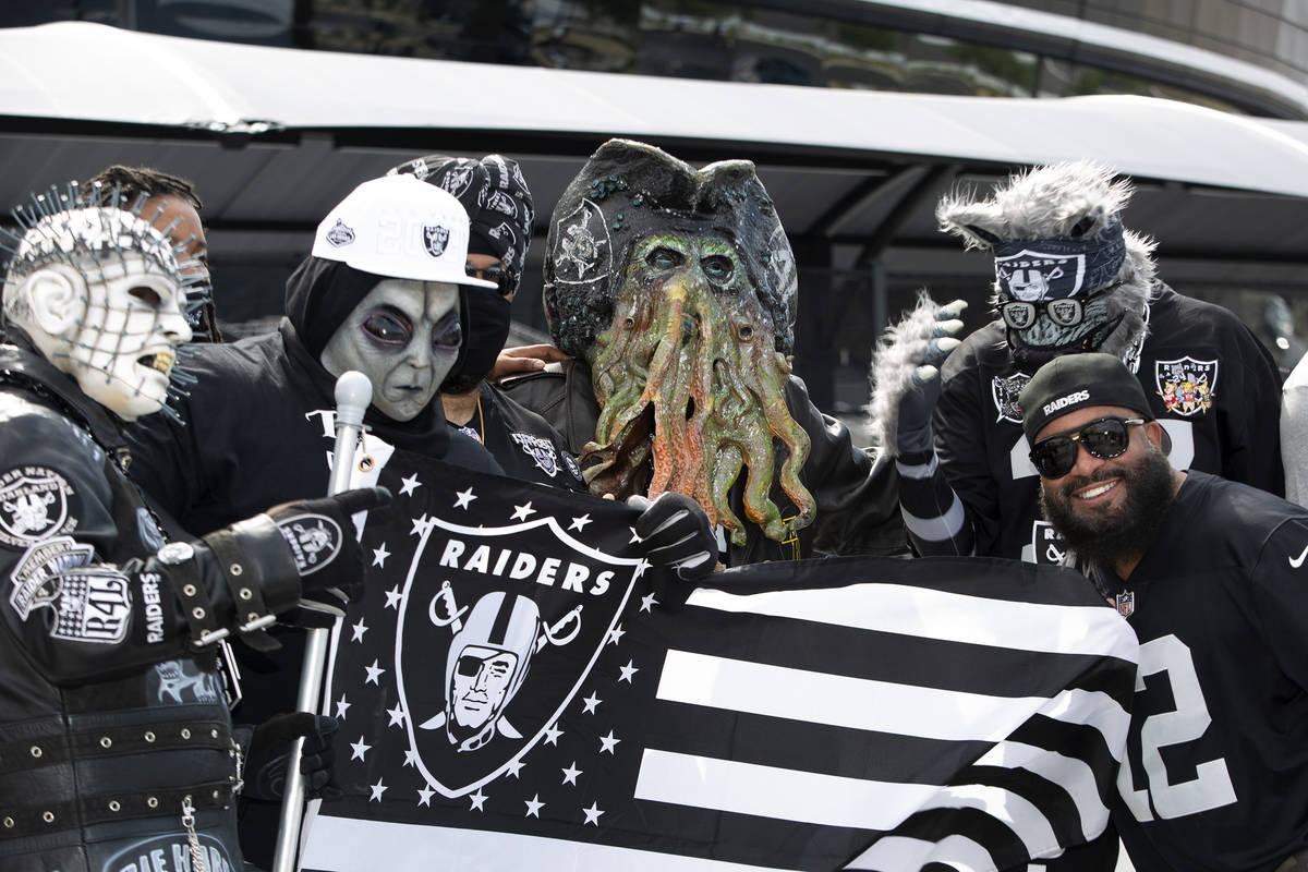 Patrick Beckett de Nueva Jersey posa para una foto con fans de los Raiders disfrazados mientras ...