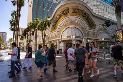 Gente camina fuera del Golden Nugget en Fremont Street Experience en el centro de Las Vegas el ...