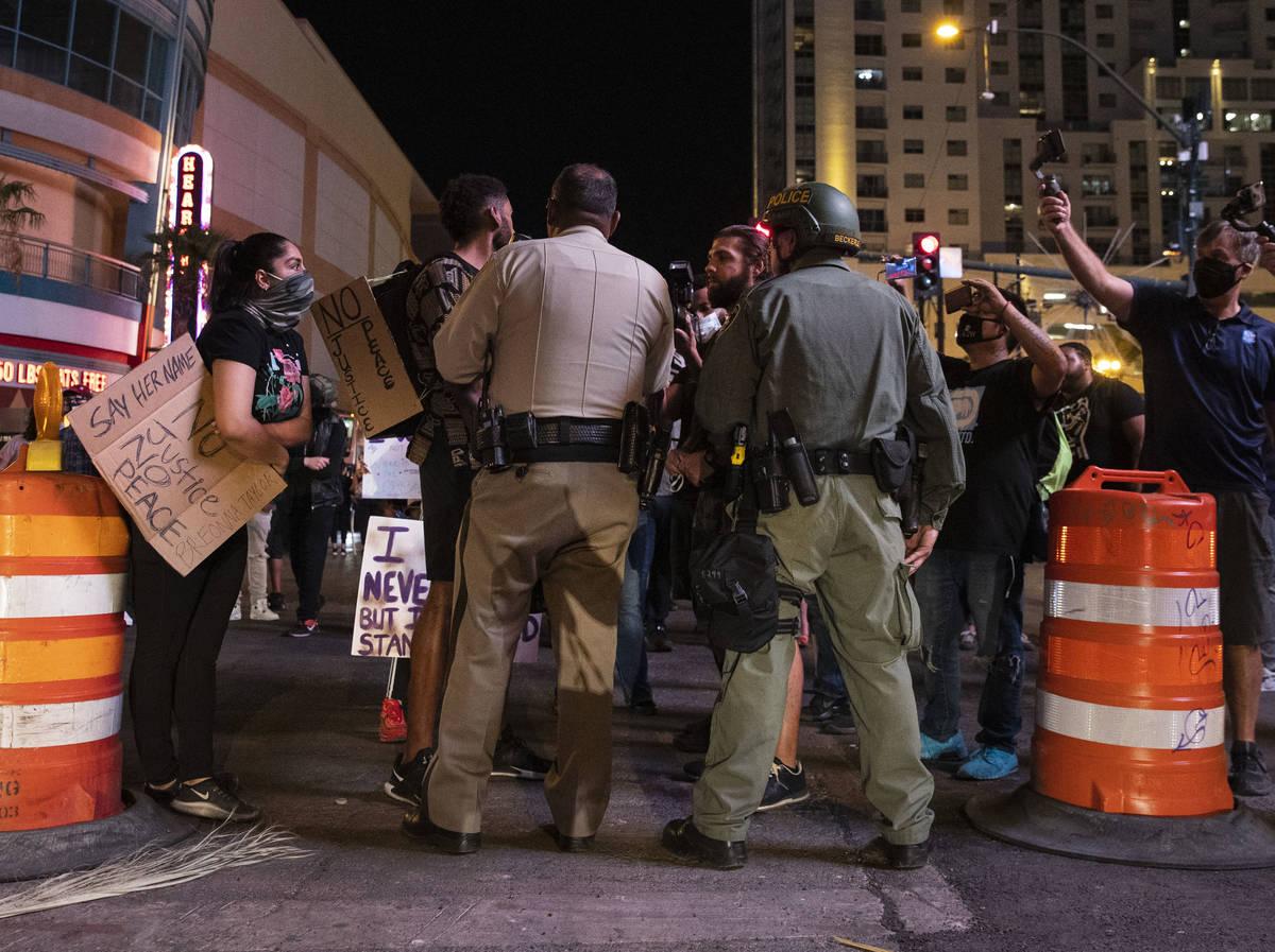Manifestantes, pidiendo justicia por la muerte a tiros de Breonna Taylor, negocian con los agen ...