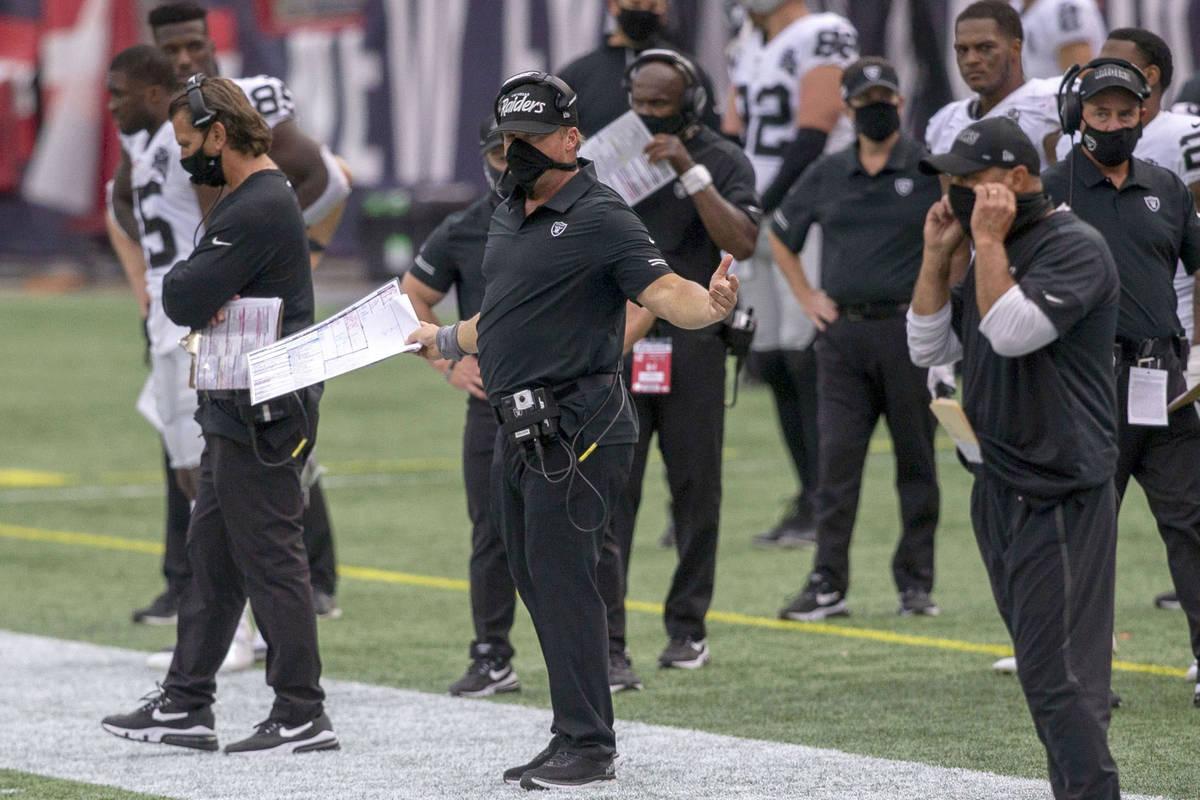 El entrenador de los Raiders de Las Vegas, Jon Gruden, centro, reacciona mientras los árbitros ...
