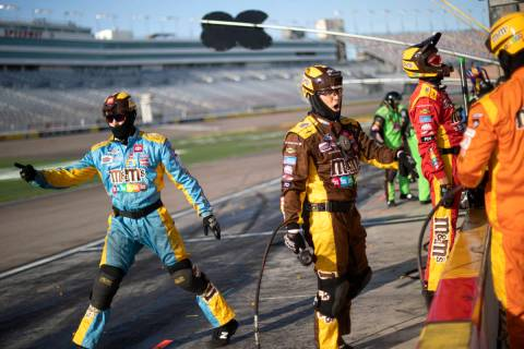 El equipo mecánico de Kyle Busch (18) envía su auto devuelta a la carrera durante una carrera ...