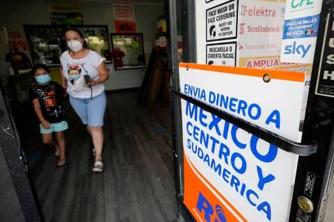 Una mujer sale de una tienda que ofrece servicios para enviar remesas a México y Centroaméric ...