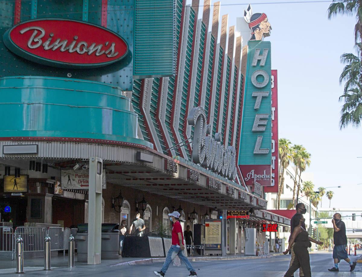 Gente camina a través de la calle Fremont con el Hotel Apache al fondo en el centro de Las Veg ...
