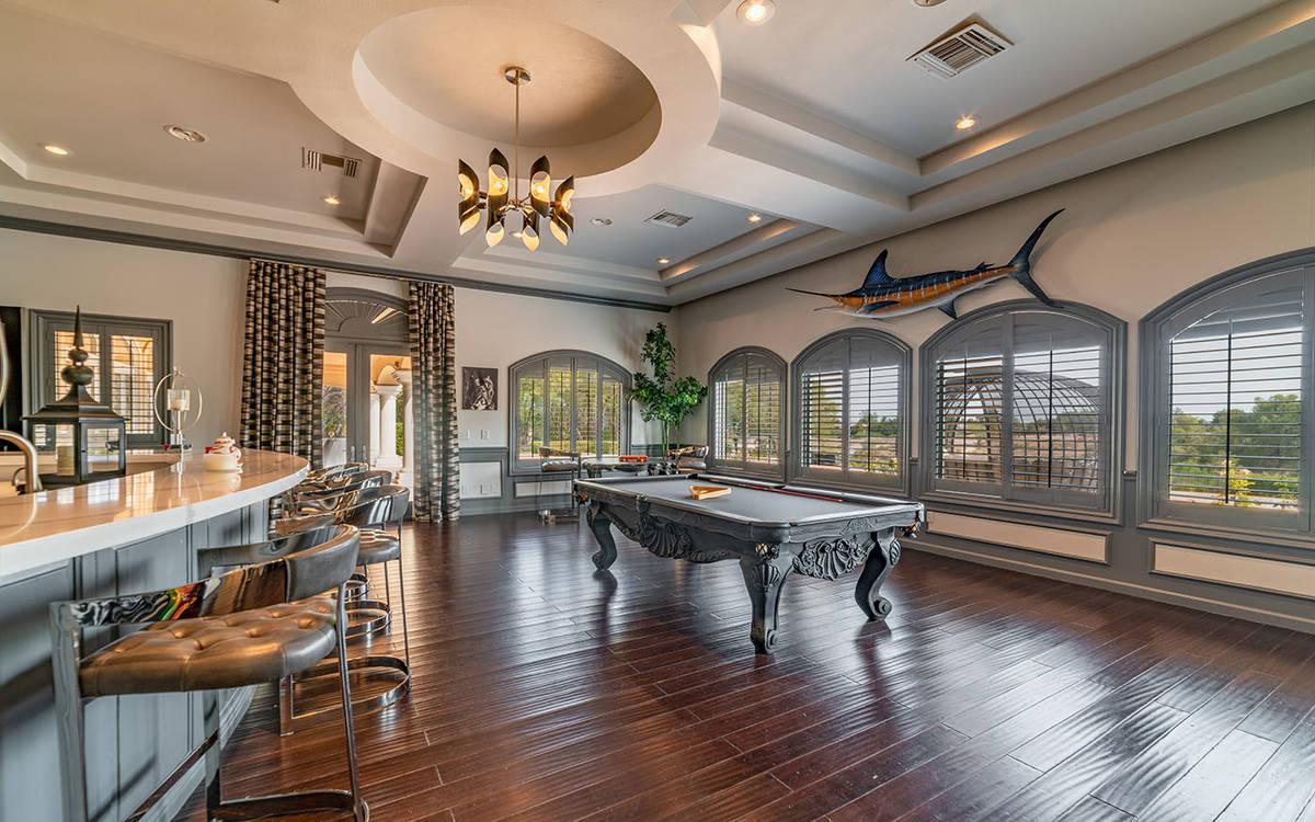El nivel principal de la casa tiene una sala de billar con un extenso bar mojado y una sala de ...