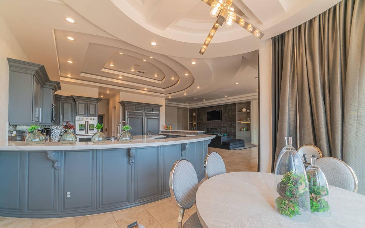La cocina tiene una paleta de colores gris y blanco, electrodomésticos mejorados y un desayuna ...
