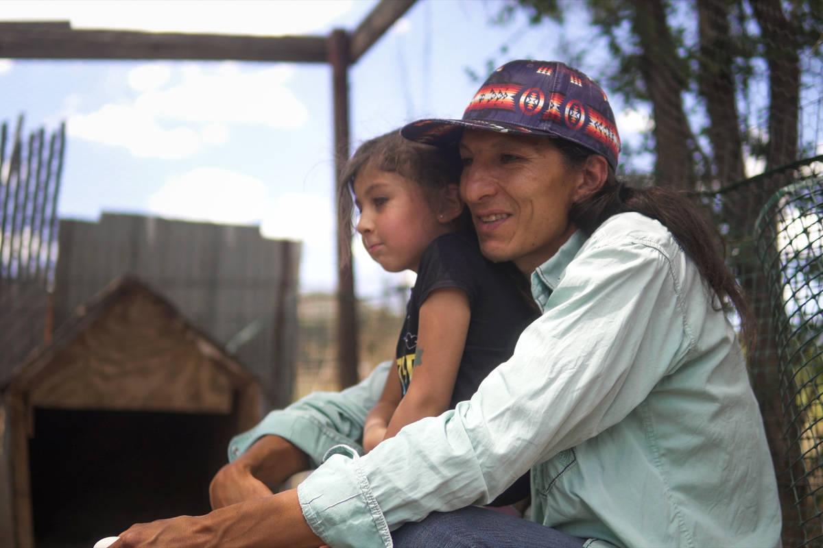 Clayson Benally se acurruca con su hija Zonnie después de alimentar a sus pollos el 29 de juli ...