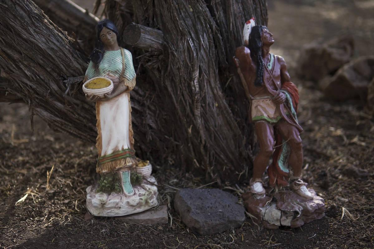 Estatuas indígenas decorativas se alinean en los árboles del patio trasero de Jeneda Benally ...