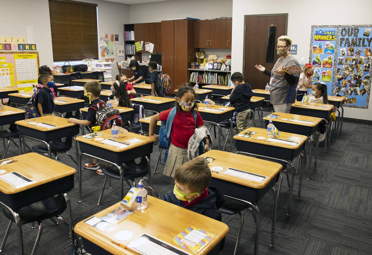 Susan Villagracia, maestra de jardín de niños, dirige a su estudiante dónde sentarse durante ...