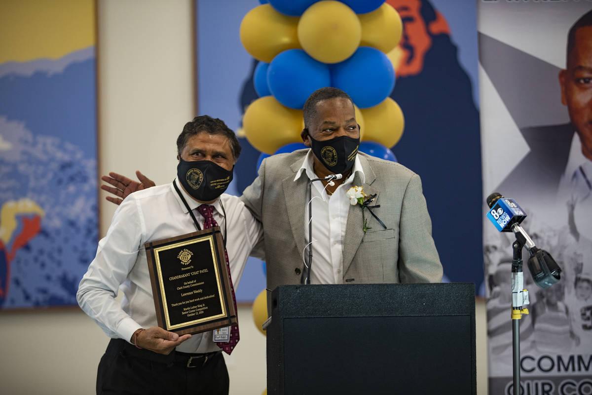 El comisionado del Condado Clark, Lawrence Weekly, a la derecha, le entrega a Chandrakant Patel ...