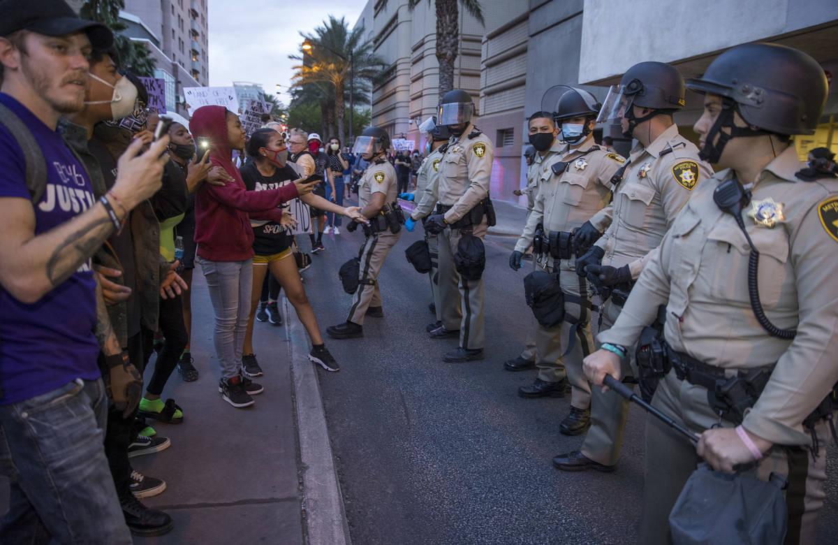 La policía de Las Vegas observa como los manifestantes se enfrentan a ellos mientras marchan a ...